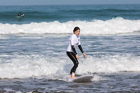 girl learning to surf in a beginner group surf lesson with SSS Surf School in Newquay, Cornwall