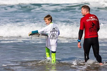 child carrying surfboard during a kids group surf lesson with SSS Surf School in Newquay